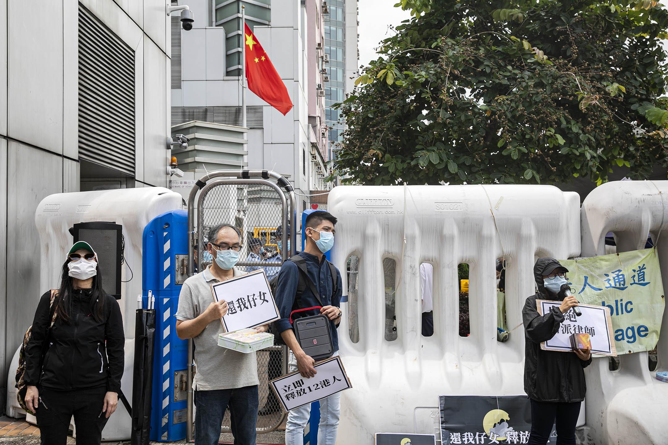 2020年9月30日,深圳檢方宣布批捕12港人,部分家屬在中聯辦門外舉牌抗議。 攝:陳焯煇/端傳媒