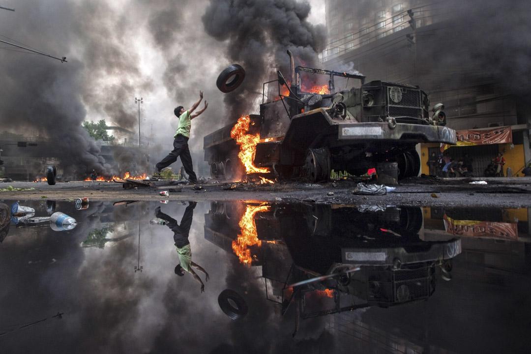 2010年5月16日曼谷,反政府抗議者紅衫軍投擲輪胎往被燒的卡車。