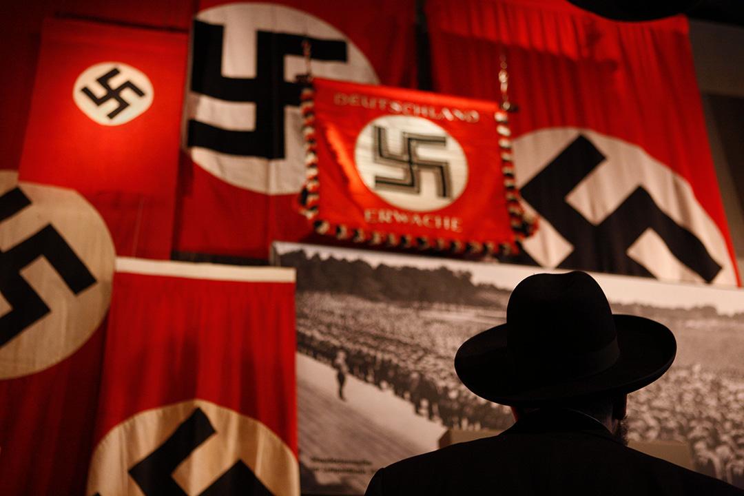 2007年1月26日耶路撒冷,大屠殺紀念館的展覽内,一名男子看著一面納粹旗幟。