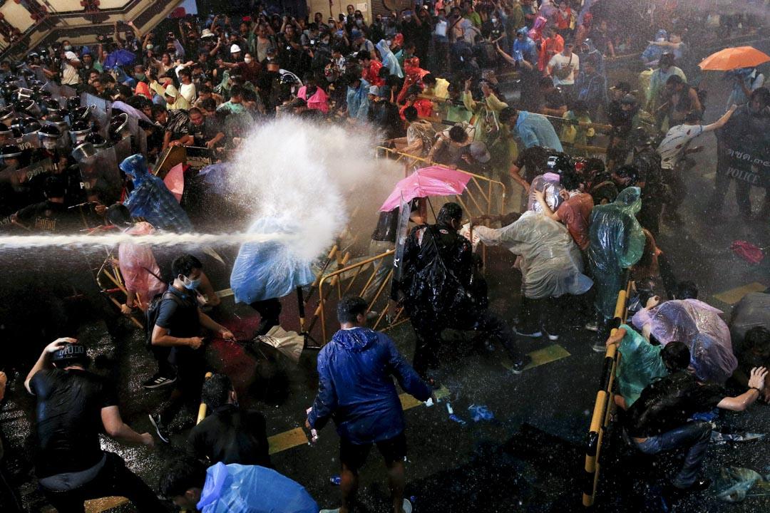 2020年10月16日泰國曼谷,示威者用雨傘抵擋警方發射的水炮。 攝:Jorge Silva/Reuters/達志影像