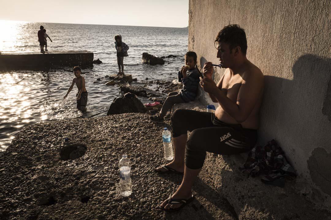 年輕的尋求庇護者在海邊休息。