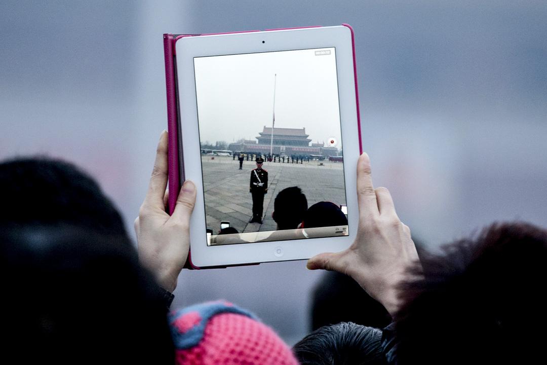 2013年3月17日,一位遊客使用平板電腦在北京天安門廣場舉行的升旗儀式上拍照。