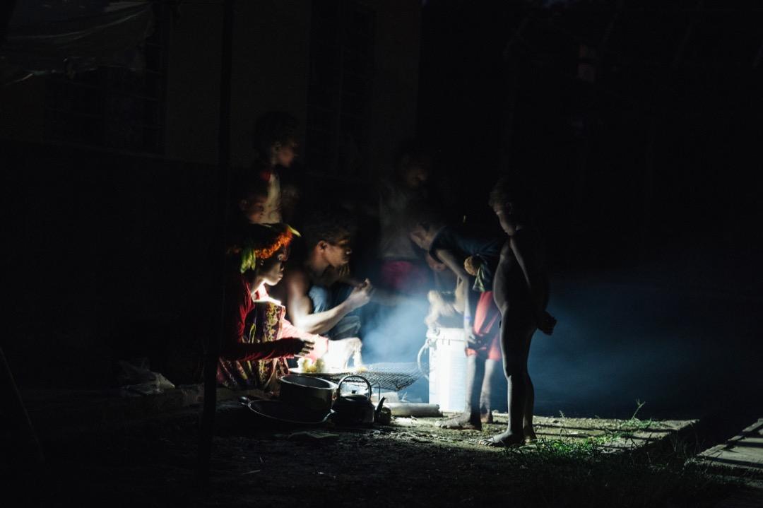 在沒有電的夜晚,巴迪族拿着手電筒照明,準備享用晚餐。