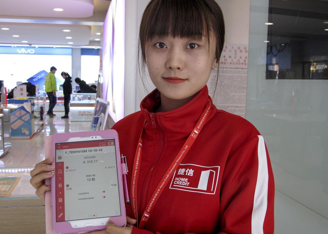 一名工作人員展示捷信集團旗下的「捷信消費金融」應用程式。