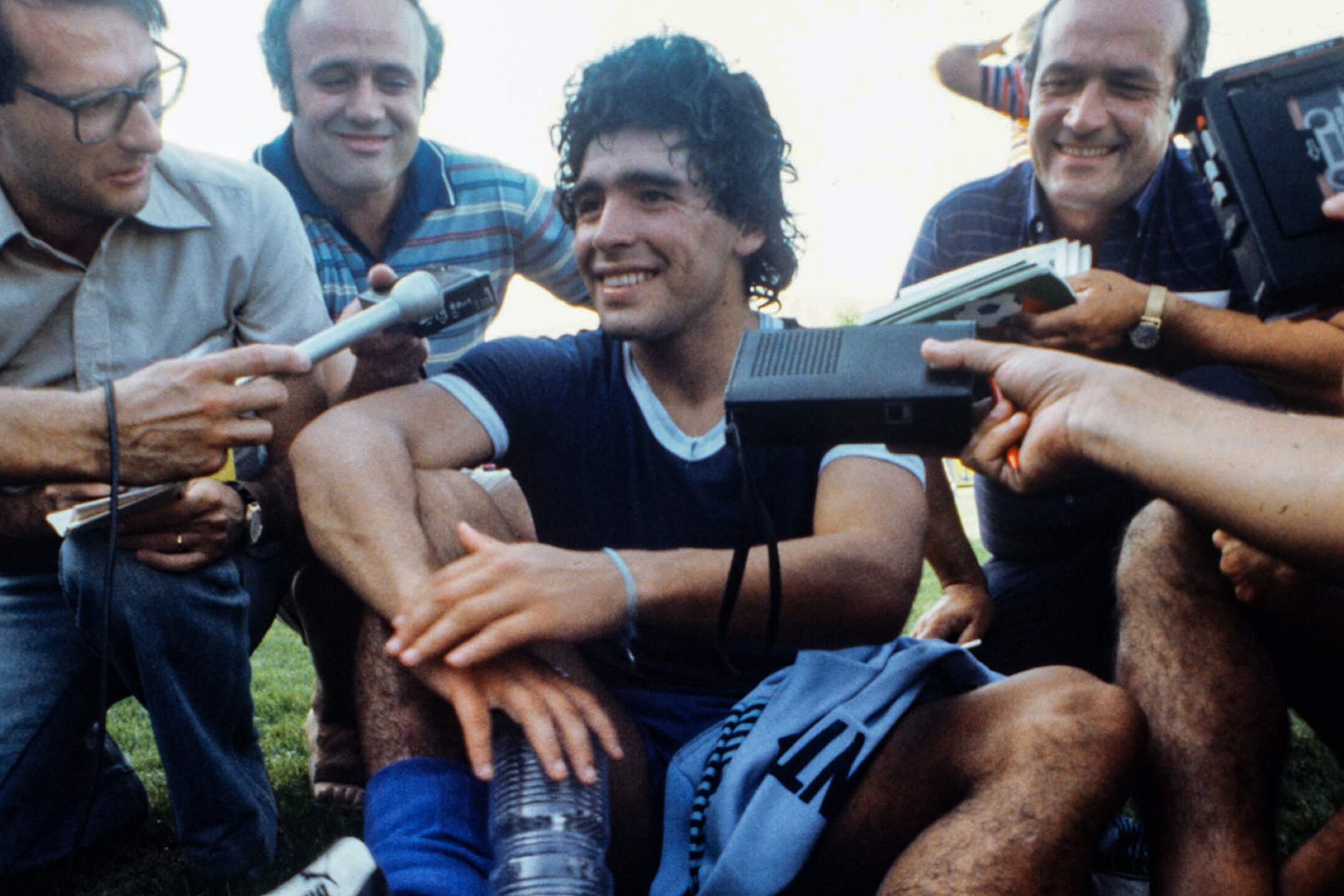 1982年6月21日,世界盃決賽周期間,球星馬勒當拿在球場上接受一眾記者採訪。 攝:Karl Staedele/picture alliance via Getty Images