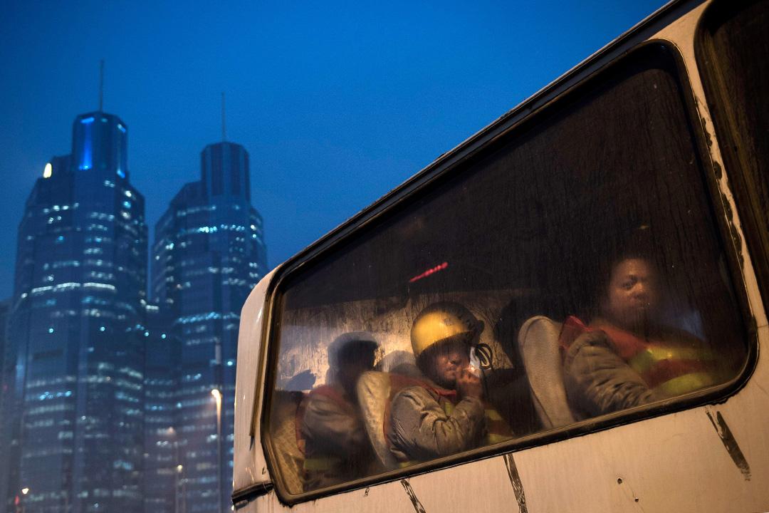 2014年12月9日北京,工人在一輛公共汽車上離開建築工地。 攝:Kevin Frayer/Getty Images