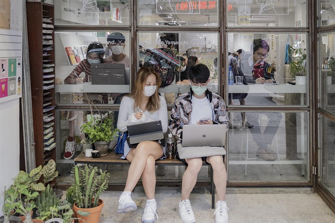 2020年10月23日香港深水埗,年青人在一家咖啡店的門外看電腦。 攝:陳焯煇/端傳媒