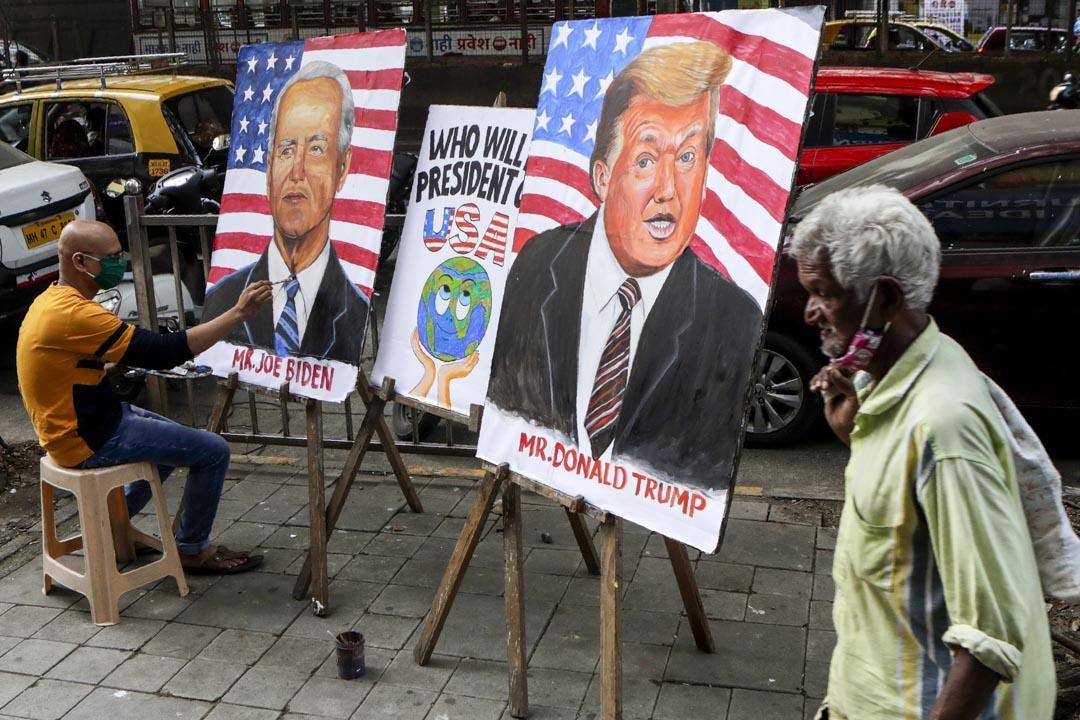 2020年10月29日,美國總統大選前夕,印度一位藝術老師在街上繪畫特朗普和拜登的畫作。 攝:Rajanish Kakade/AP/達志影像