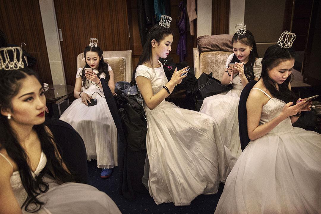 2016年3月19日北京,初次登台的表演者在後台看著手機。 攝:Kevin Frayer/Getty Images
