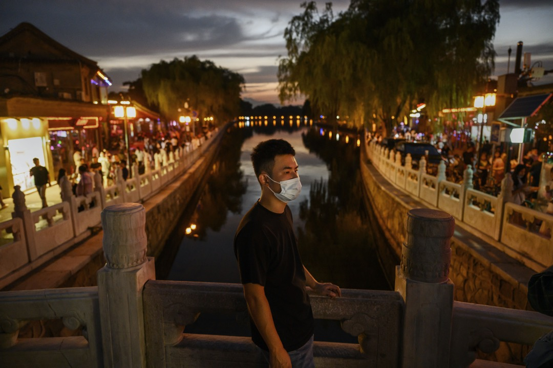 2020年8月19日,一名戴著口罩的男子站在北京後海岸邊。 攝:Kevin Frayer/Getty Images