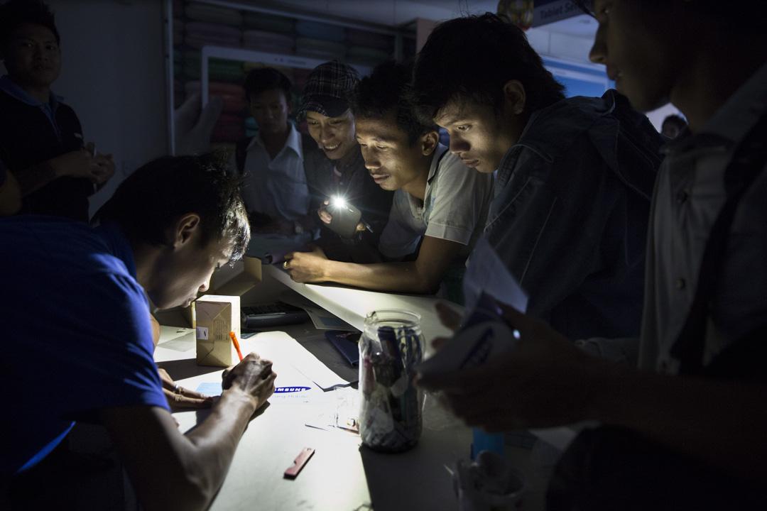 2014年11月6日,緬甸仰光停電,工人在商店用手機燈照明。