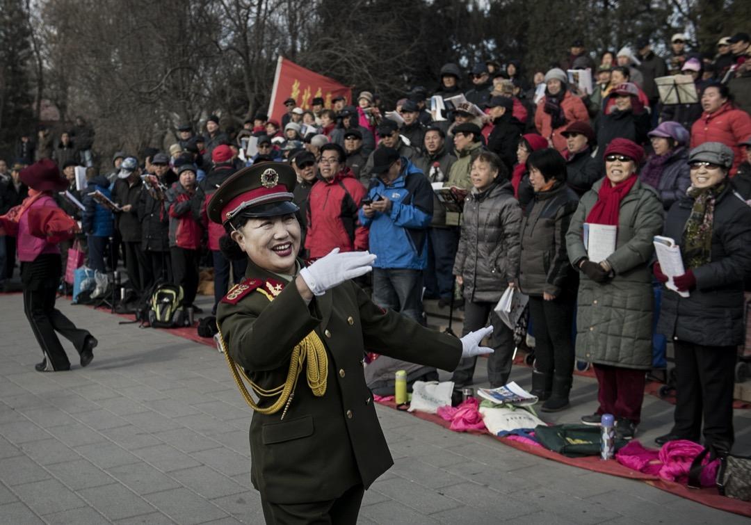 一名穿著解放軍服裝的女子在北京一個公園裏領唱愛國歌曲。 攝:Kevin Frayer/Getty Images