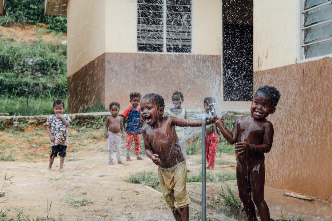 在安裝淨水過濾器後,孩子們開着水龍頭噴水玩樂。