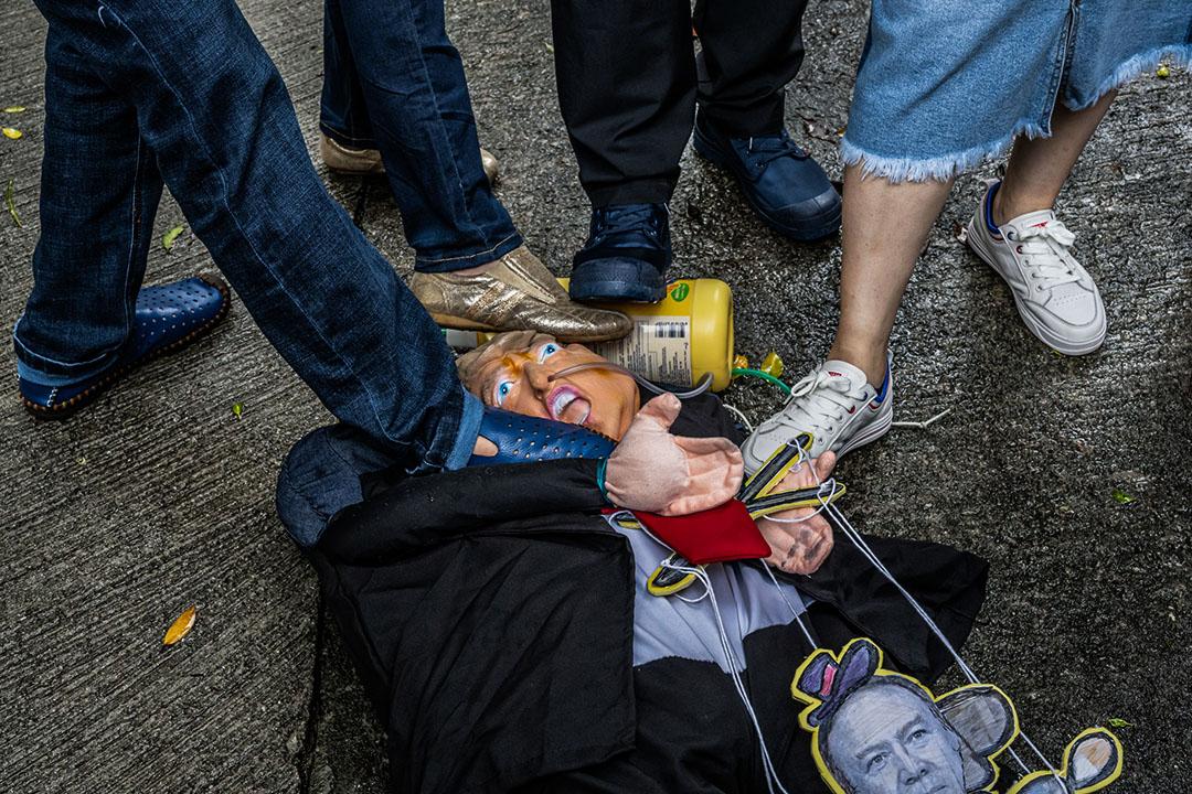 2020年5月30日香港美國領事館外,中國政府的支持者踩在特朗普的面具上。