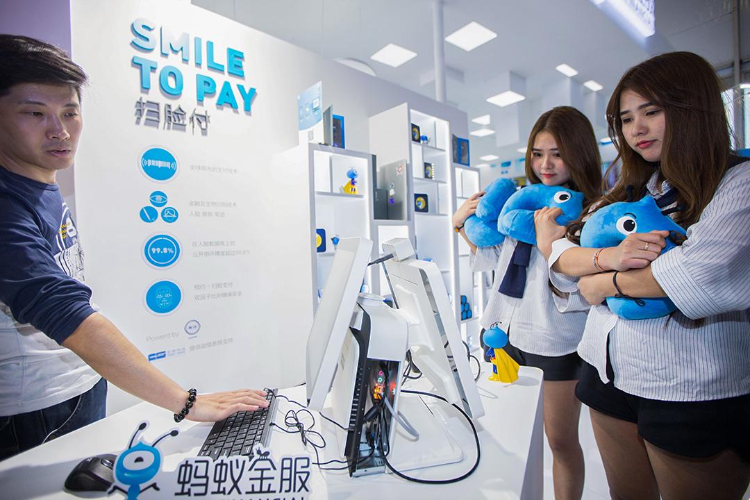 2016年10月12日杭州,兩名女生在螞蟻集團的攤位通過面部識別付款。