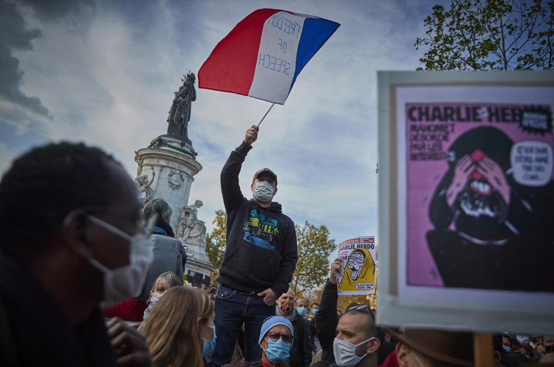 2020年11月18日,法國巴黎共和廣場舉行反恐守夜活動,一名參加者揮舞著寫著「言論自由」的法國三色旗。