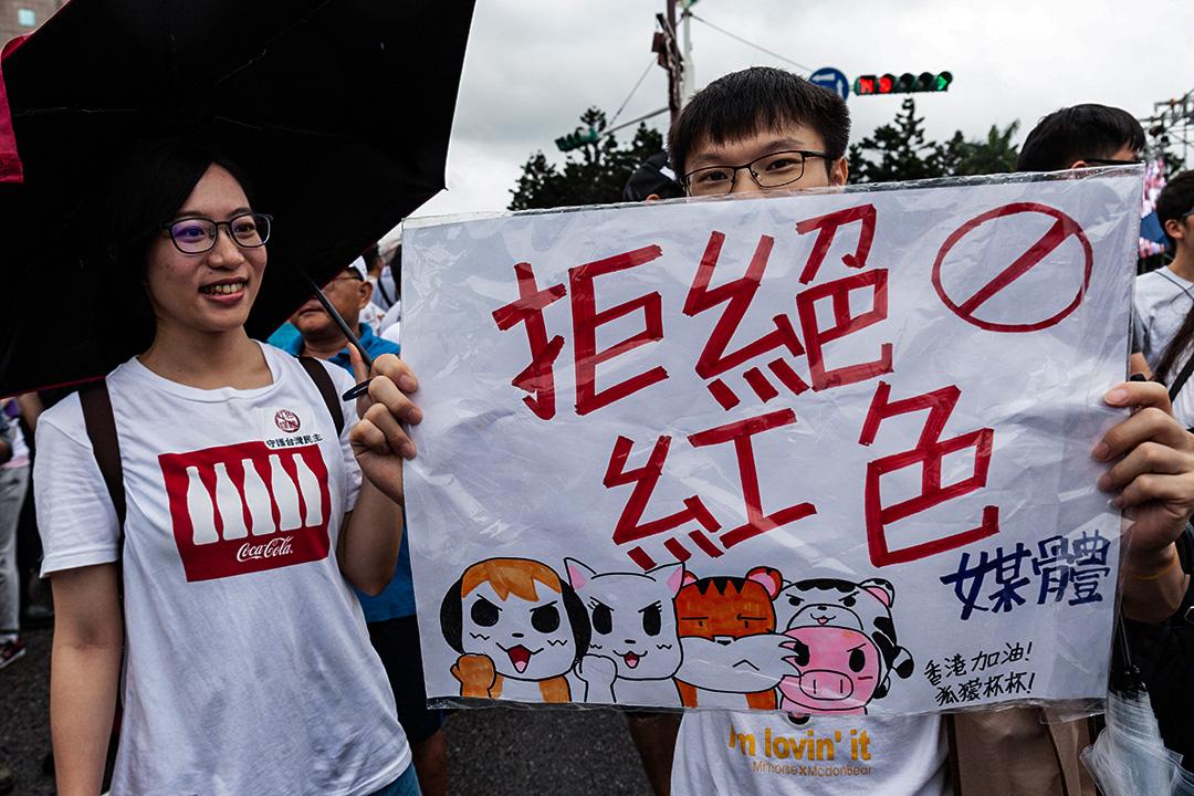 2019年6月23日台北,抗議者站在大雨中舉著標語示威。