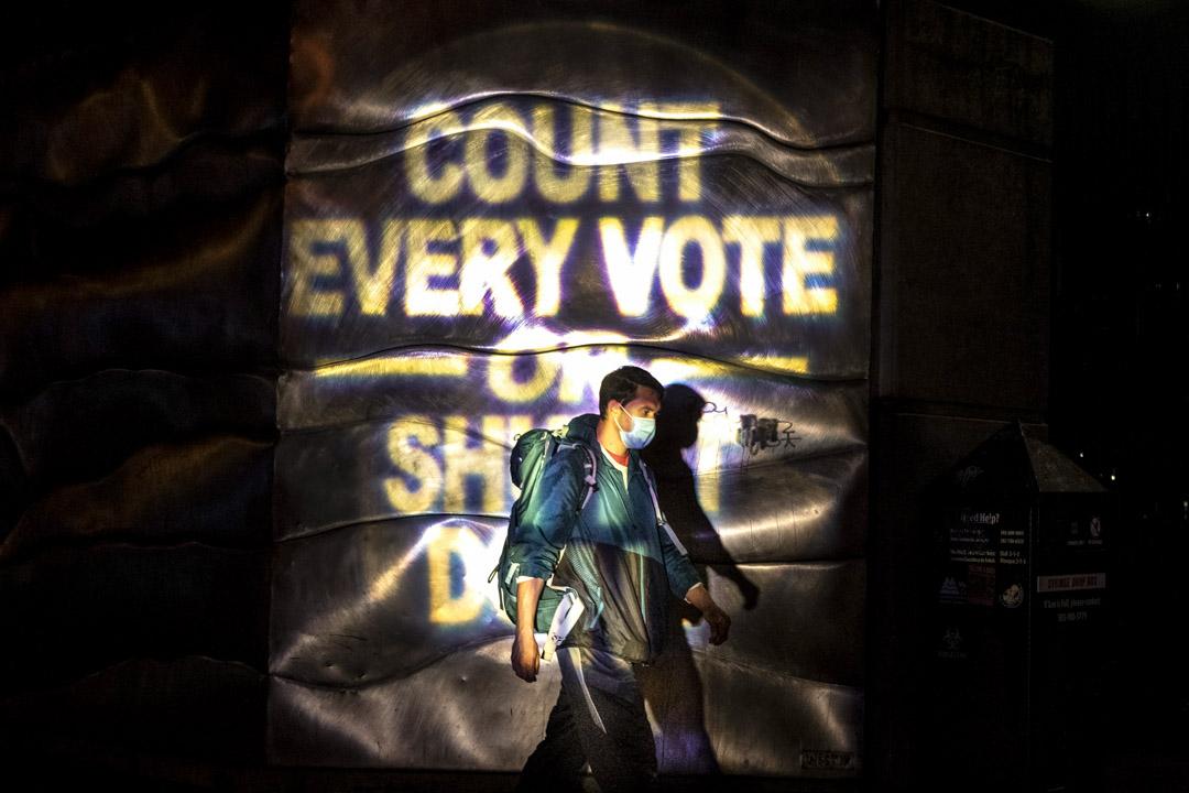 2020年11月4日俄勒岡州波特蘭,總統選舉後的抗議活動中,一名男子經過拜登支持者的口號。 攝:Paula Bronstein/AP/達志影像