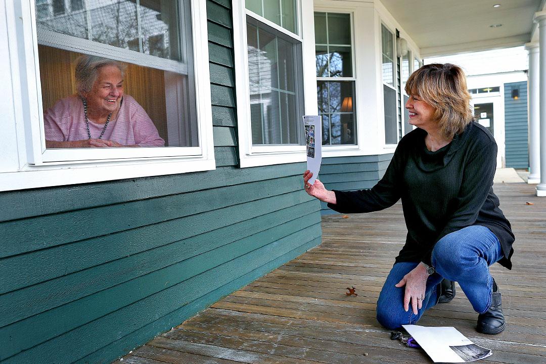 2020年3月28日美國馬薩諸塞州,86歲的母親在屋內,她的女兒到訪並蹲在外面向媽媽展示孫兒的一些近照。 攝:John Tlumacki/The Boston Globe via Getty Images