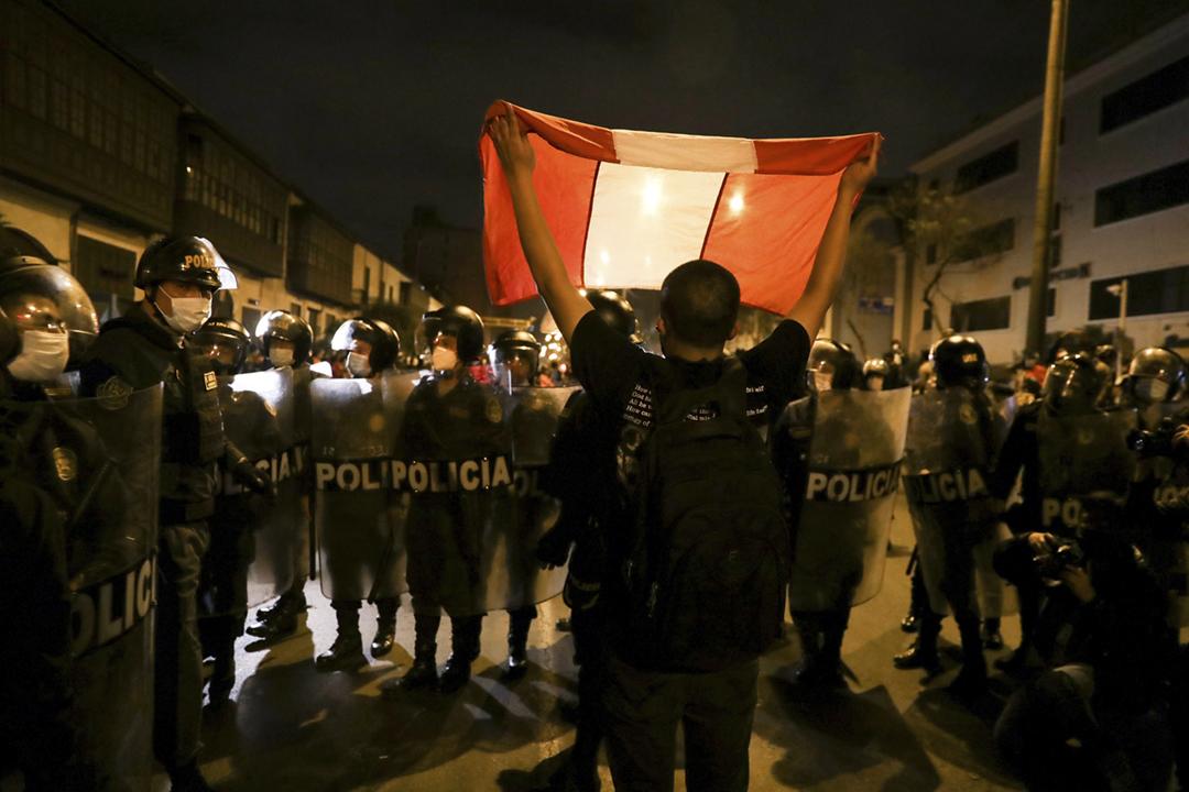 2020年11月10日在秘魯首都利馬,一名抗議國會彈劾總統的示威者在警察防線前高舉國旗。 攝:Sebastian Castaneda / Reuters