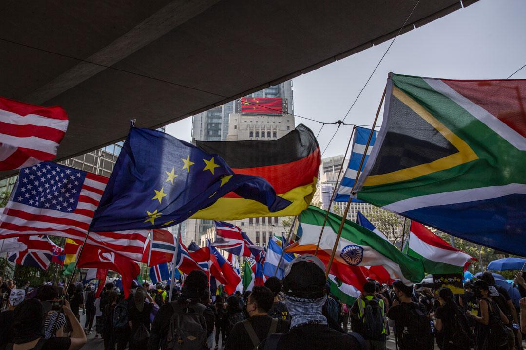 2019年10月1日,港島有遊行,參加者手持多國國旗途經中國銀行大廈。
