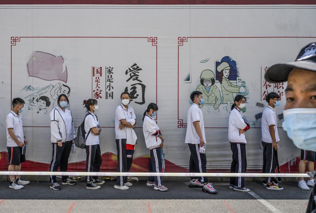 2020年7月7日,北京一所中學的學生排隊進入一所學校參加全國高考,背後有愛國的宣傳。 攝:Kevin Frayer/Getty Images