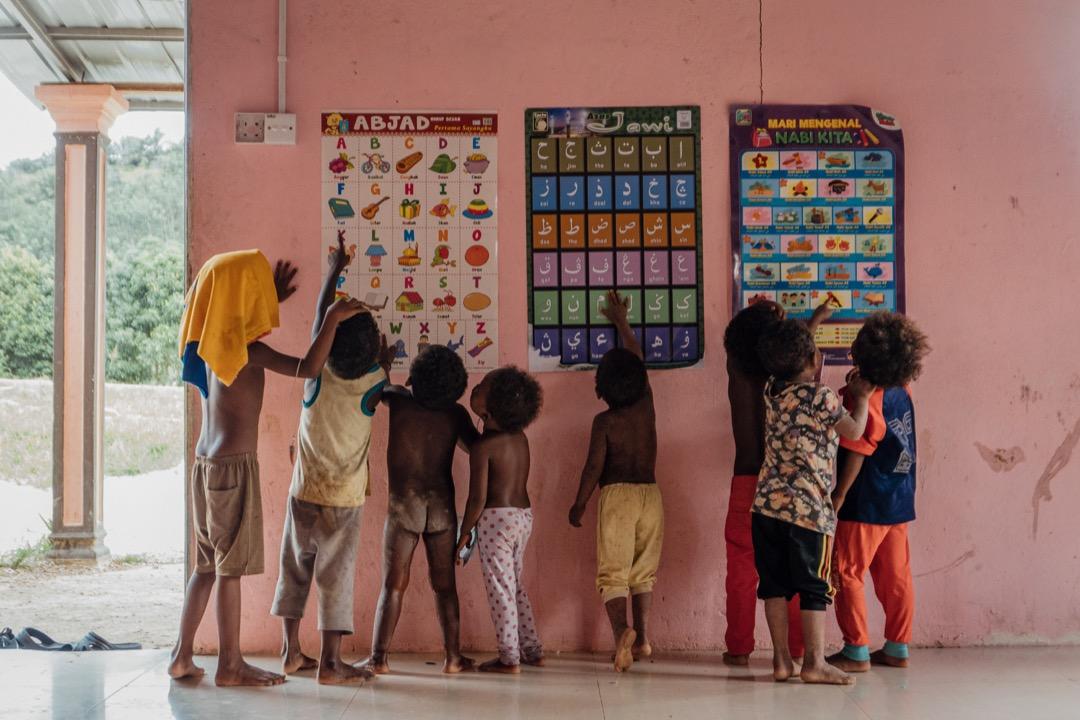 一群巴迪族小孩在清真寺內,看著貼在牆上的爪夷文字母,朗誦阿拉伯經文。