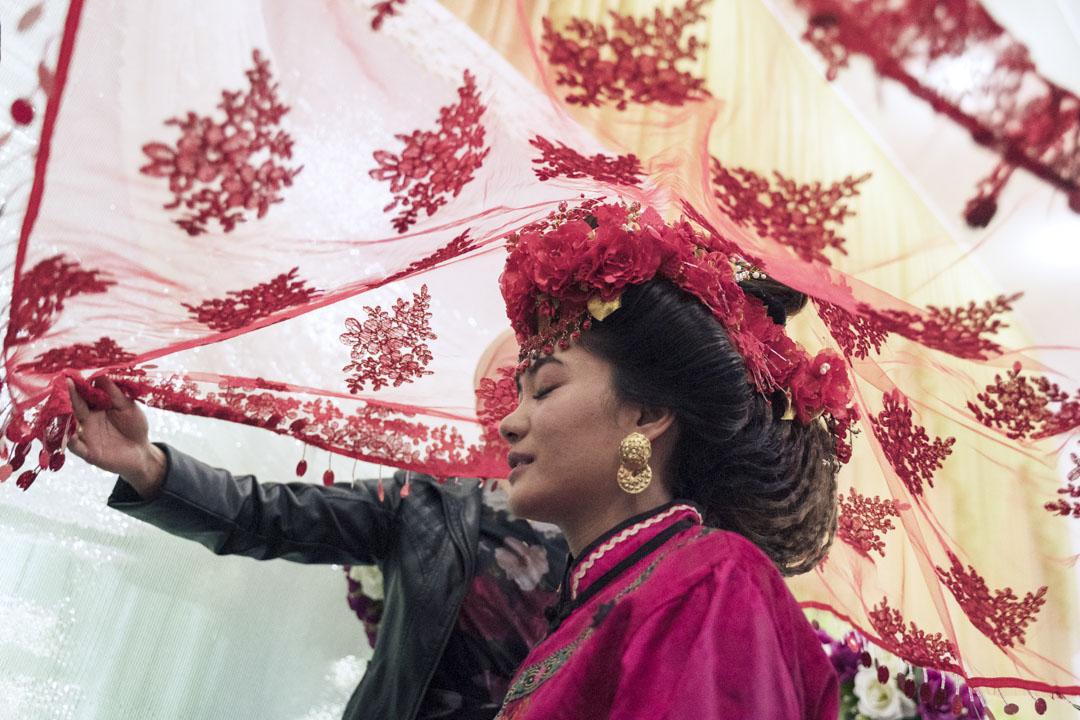 2019年10月27日,吉爾吉斯斯坦,米爾方, 麥當娜舉行婚禮時前往新郎之家之前被紅色長袍遮蓋。東干遵循19世紀傳統的回族婚禮並實行內婚制,但由於人口不斷縮小,他們停止內婚制習俗,並允許東干族與其他種族結婚。 攝影:嚴居駿