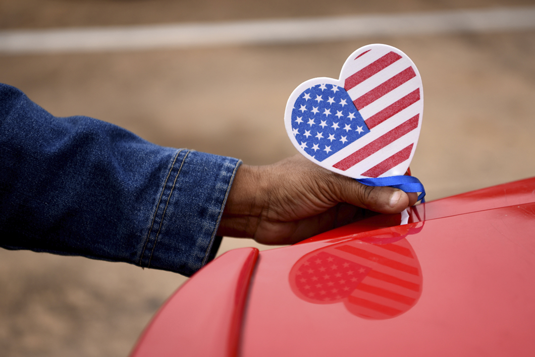 2020年11月1日、美國總統大選前的最後一個週日,競逐連任的共和黨候選人特朗普(Donald Trump)走訪五個搖擺州份,而民主黨候選人拜登(Joe Biden)則在賓夕凡尼亞州造勢。圖為美國一名民眾正在裝飾汽車,呼籲鄰舍投票。 攝:Callaghan O'Hare / Reuters