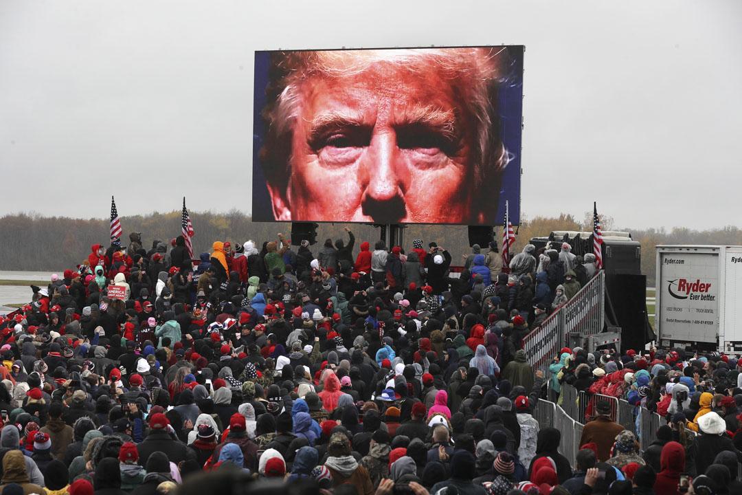 2020年10月27日,密歇根州蘭辛市的機場舉行的共和黨總統競選集會,支持者在冷雨中觀看直播中特朗普的樣子。