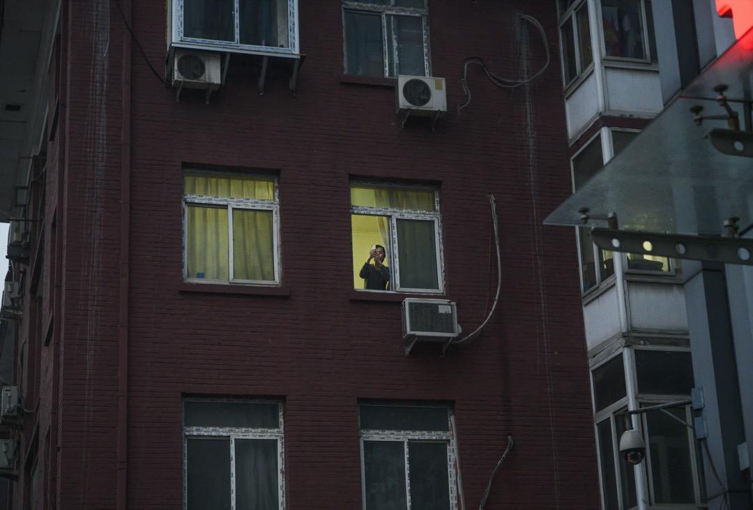 2020年3月6日,北京一所住宅內,一位男子向窗外拍攝。北京當局要求所有進入北京的人進行14天強制隔離。