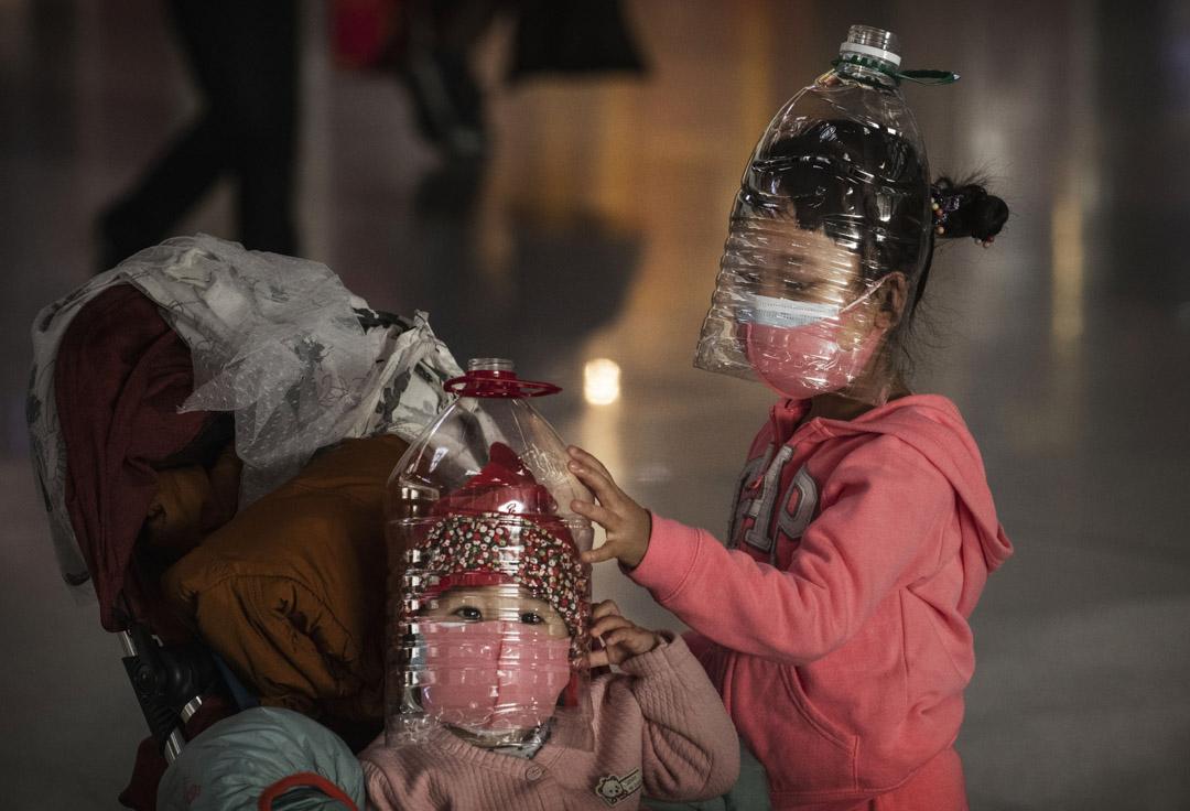 2020年1月30日,新冠病毒剛剛在武漢爆發,北京首都機場有孩子佩帶著以塑料瓶作為臨時的自創保護和防毒面具。