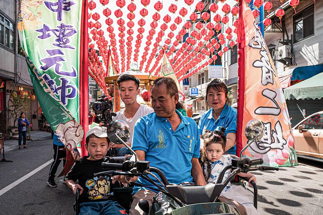一名埔里鎮民帶著孩子參與祭典。