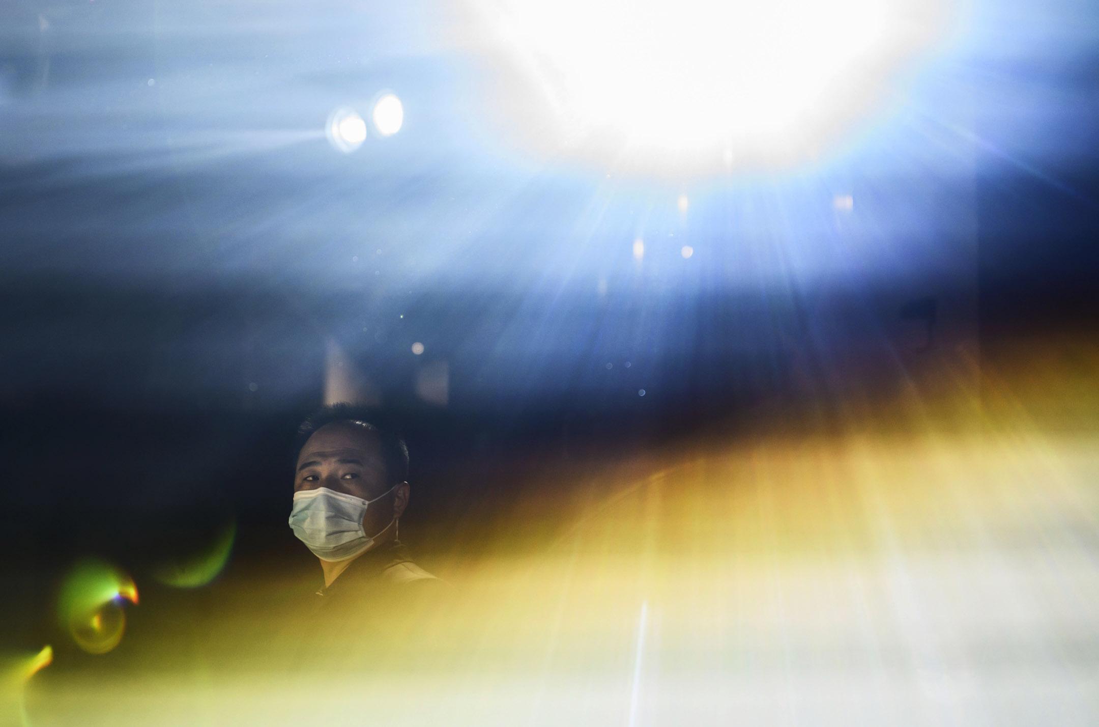 2020年11月6日,北京的一家智能手機公司的發布會上,一名保安戴著防護口罩。 攝:Kevin Frayer/Getty Images