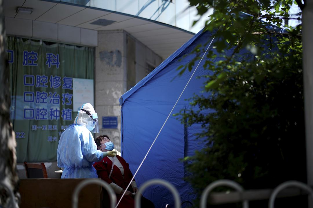 2020年4月13日在中國湖北省武漢市,醫護人員為一名女士進行病毒檢測採樣。 攝:Aly Song / Reuters