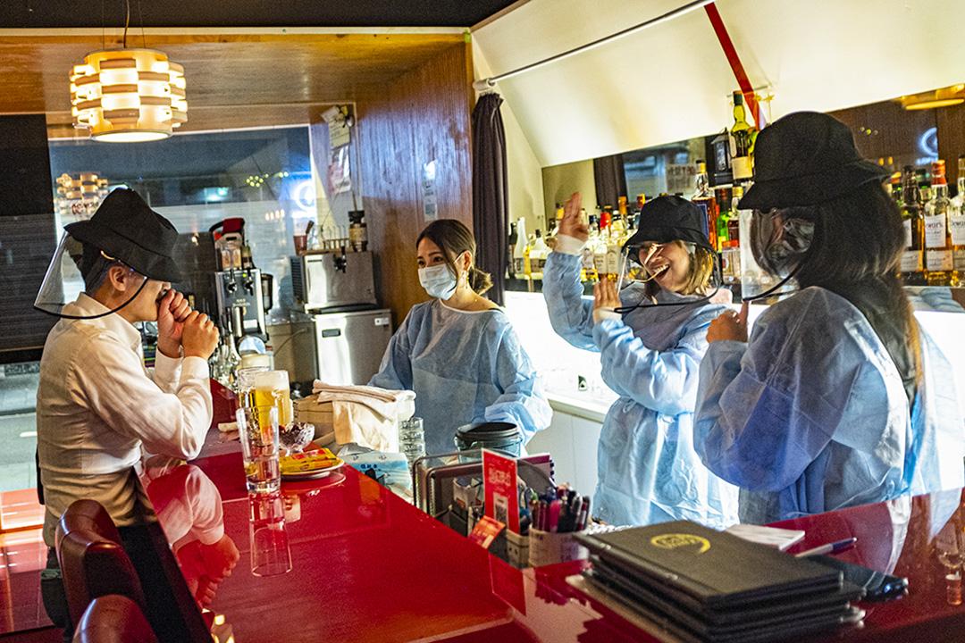 2019冠狀病毒疫情期間,一間酒吧內的職員穿上防護衣工作。