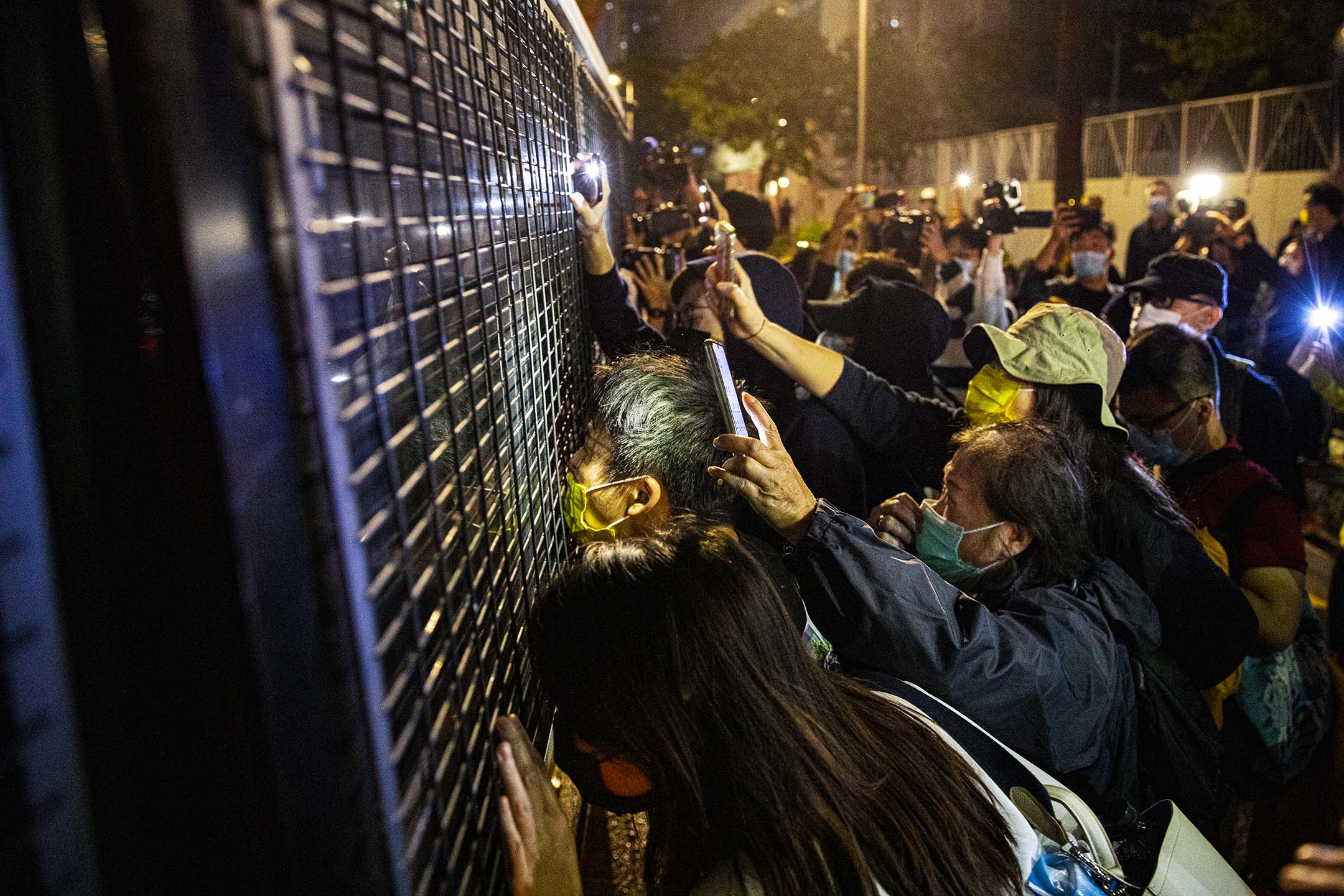 2020年12月2日,法庭外的支持者送別被判入獄的周庭、黃之鋒與林朗彥,拍打一架囚車的車窗。 攝:陳焯煇/端傳媒