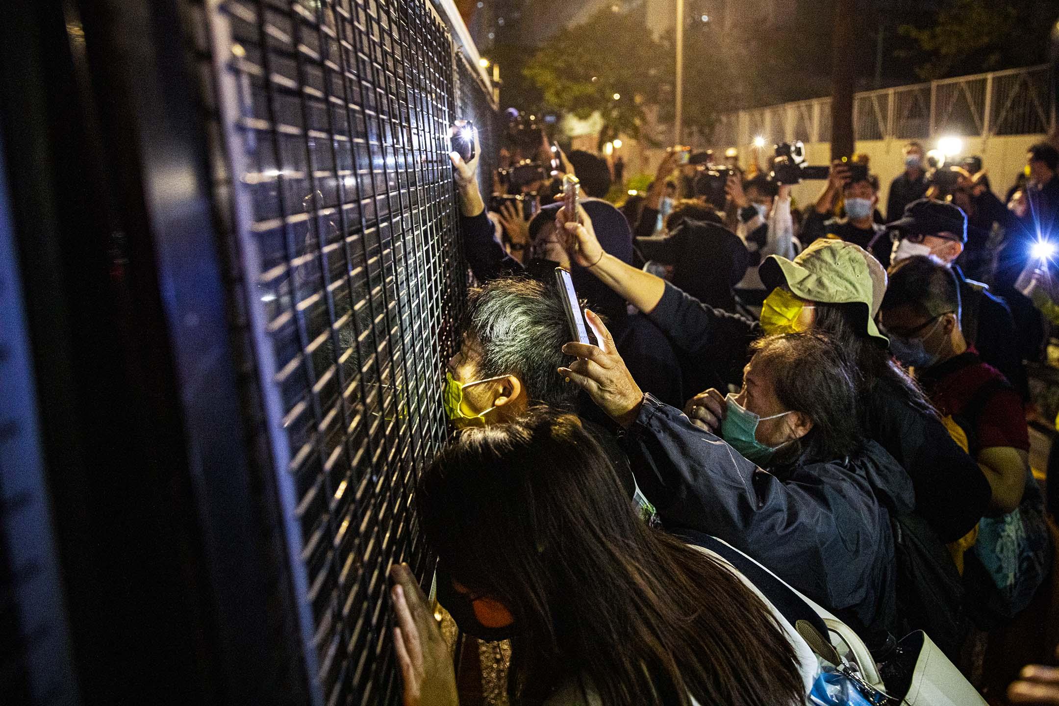 2020年12月2日,西九龍裁判法院,法庭外的支持者送別被判入獄的周庭、黃之鋒、林朗彥和其他因反修例運動而入獄的示威者,拍打一架囚車的車窗。