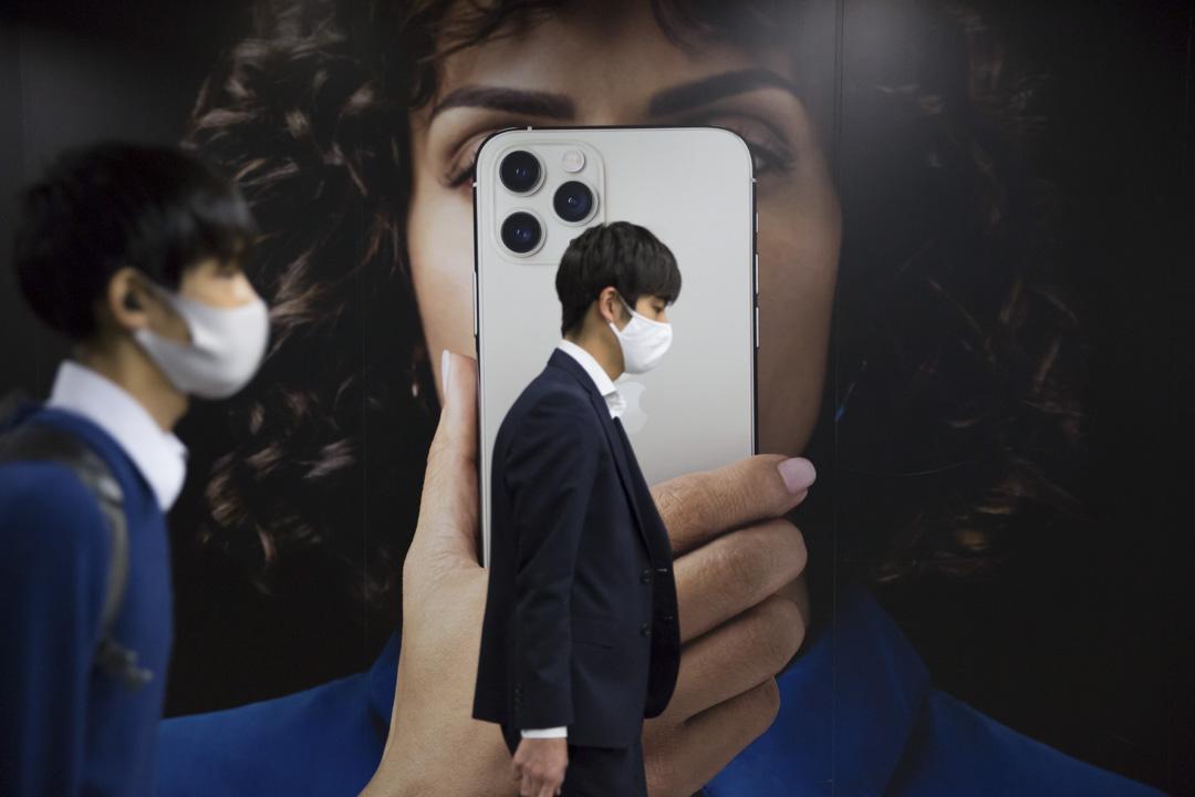 2020年10月30日,東京戴著口罩的市民在新iPhone的廣告板前走過。 攝:Stanislav Kogiku/SOPA Images/LightRocket via Getty Images