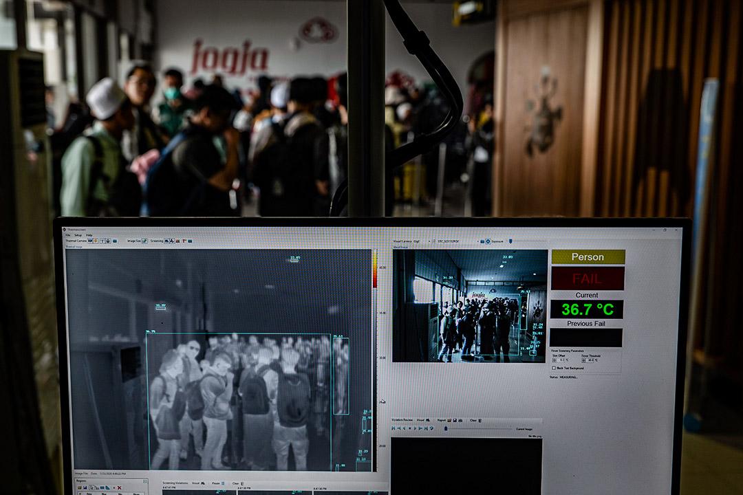 2020年1月23日印尼阿迪蘇西普托國際機場,乘客通過一台熱感掃描器。
