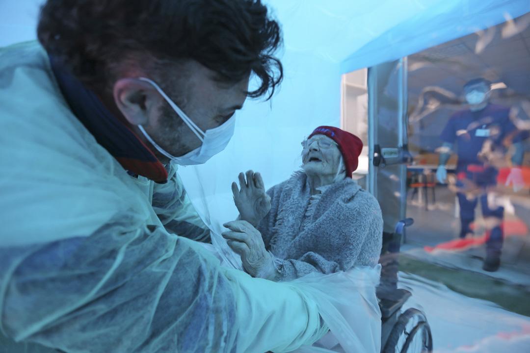 2020年12月21日,意大利一家老人院,一個男人通過塑料薄膜擁抱他的祖母。