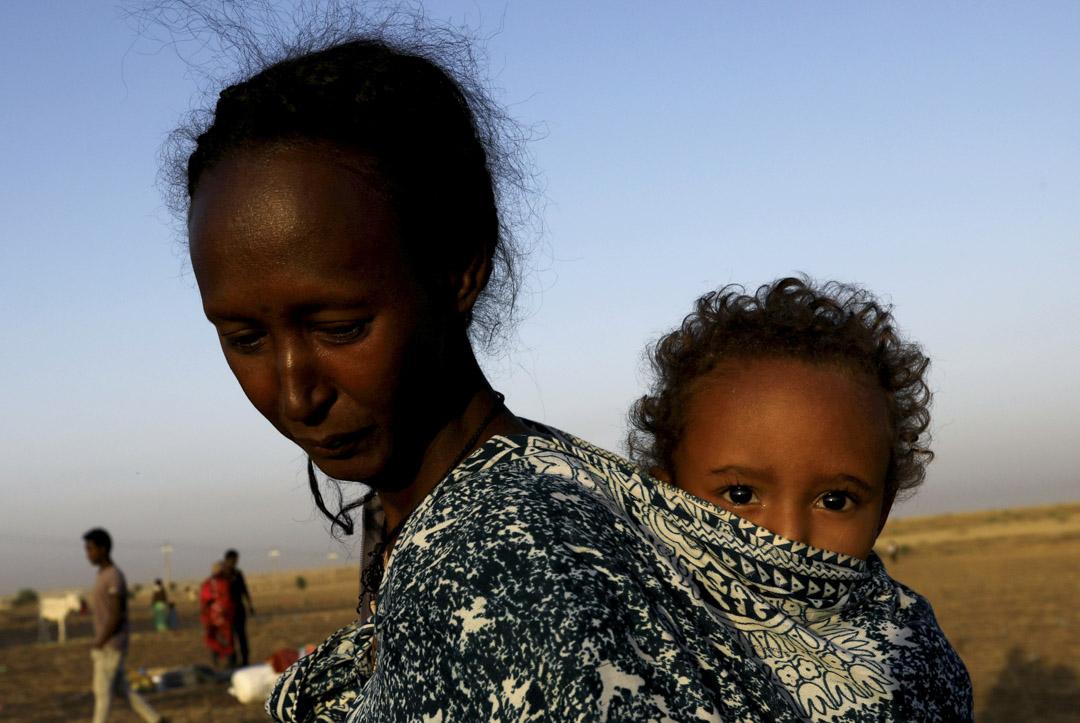 2020年11月22日,埃塞俄比亞的提格雷持續的內戰,一名母親與她的孩子逃離當地湧入鄰國蘇丹東部邊境地區。