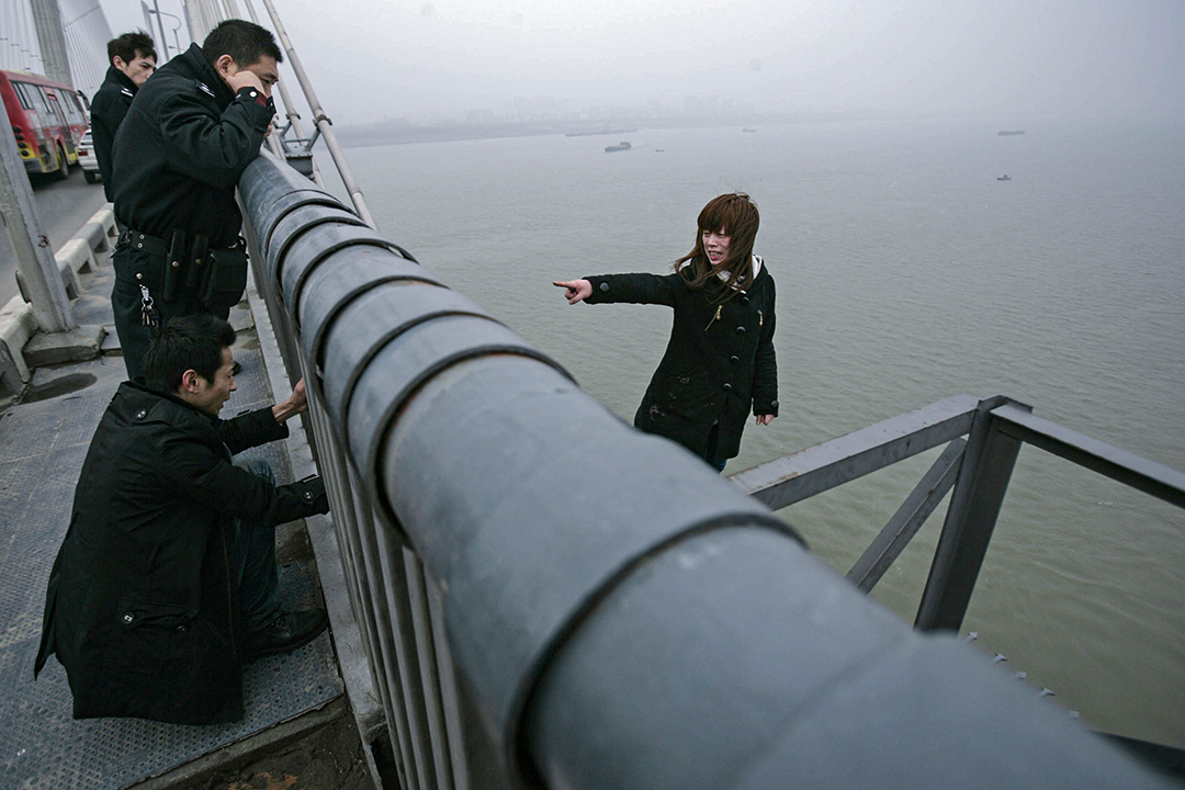 2010年2月26日武漢,一名男子試圖說服於長江企圖跳橋的女友。 攝:Feature China/Barcroft Media via Getty Images