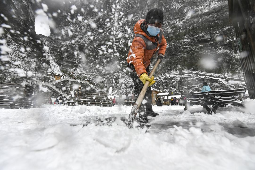 2020年12月5日,中國湖南省張家界市剛迎來今冬第一場雪,天門山一名工作人員正在清理積雪。湖南省發改委指,該省今年入冬早、降溫快,電力負荷快速攀升,宣佈全省啟動「有序用電」。 攝:Shao Ying / VCG via Getty Images