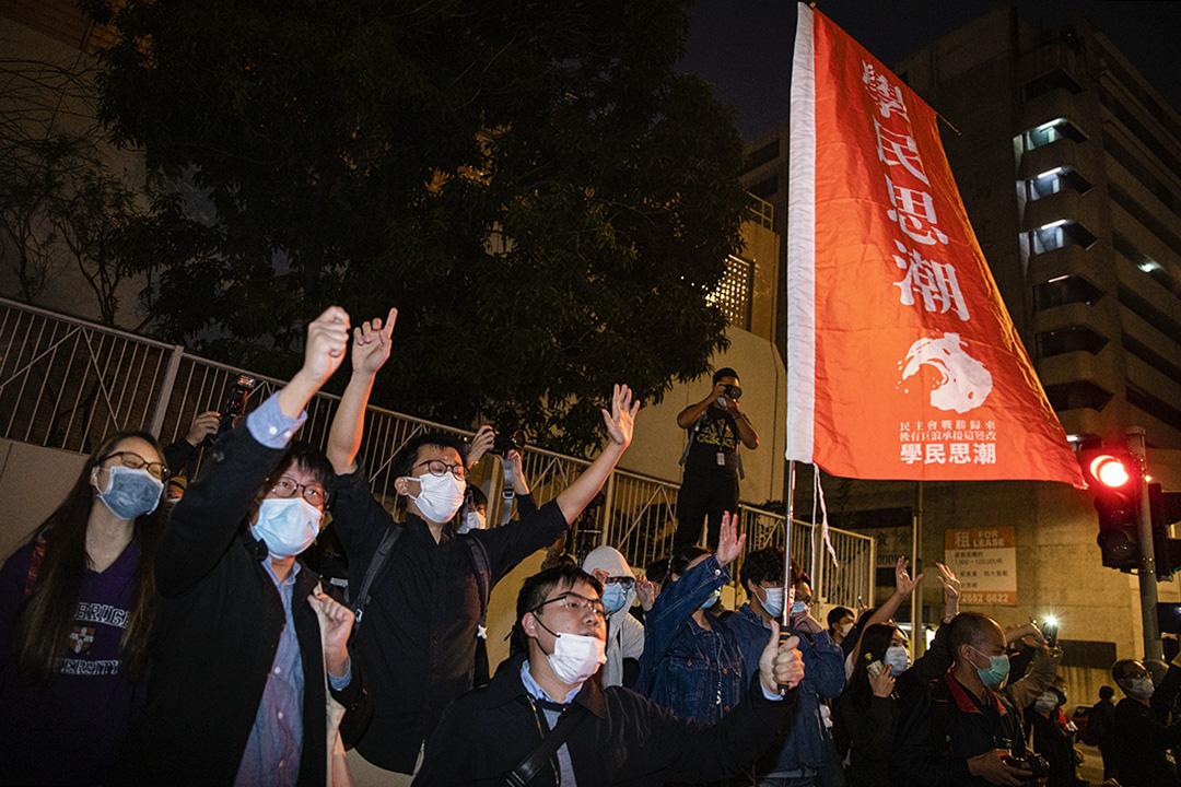 2020年12月2日,法庭外的支持者送別被判入獄的周庭、黃之鋒與林朗彥,有人拿著學民思潮的旗幟送別。