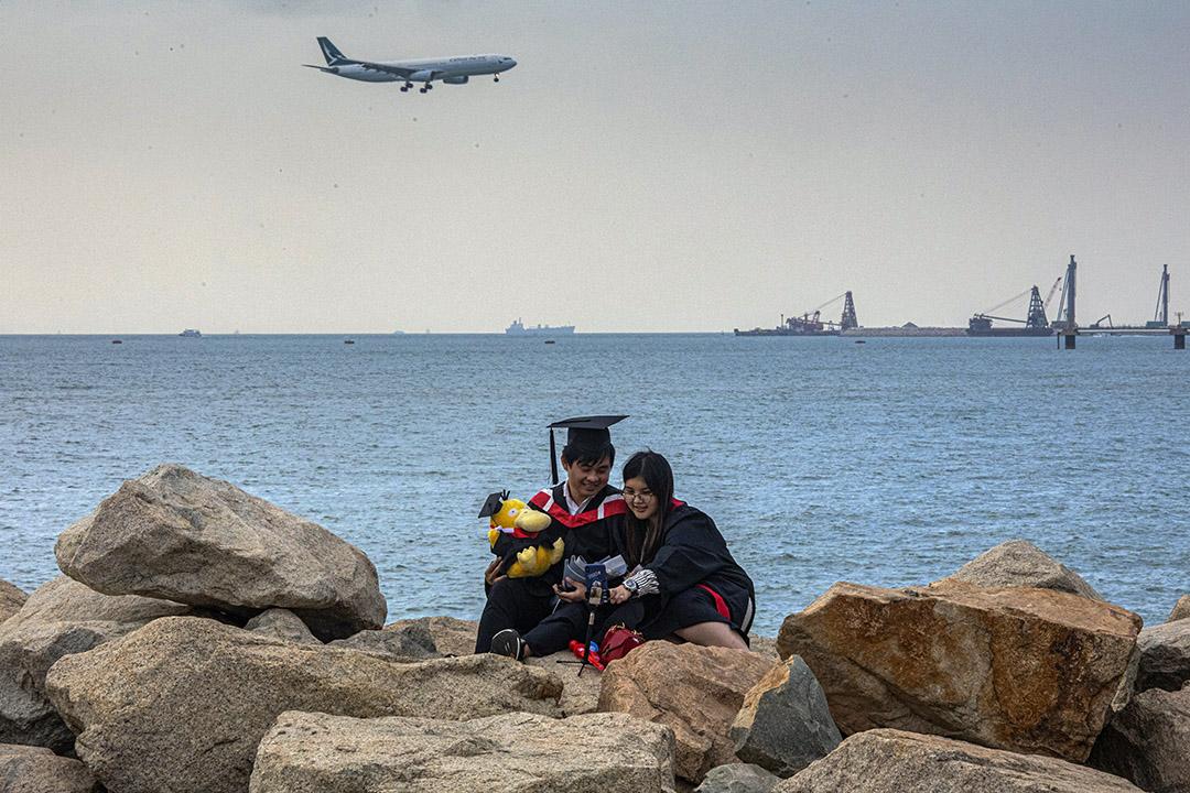 2020年11月30日香港國際機場外,一架國泰航空飛機降落,一對情侶拍畢業照。