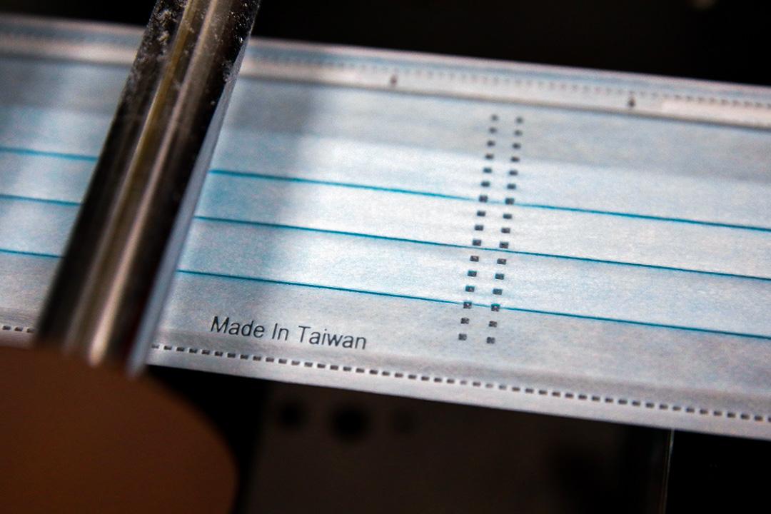 """2020年6月12日,台灣桃園的口罩廠生產線上,防護口罩壓印了""""台灣製造""""字樣。"""