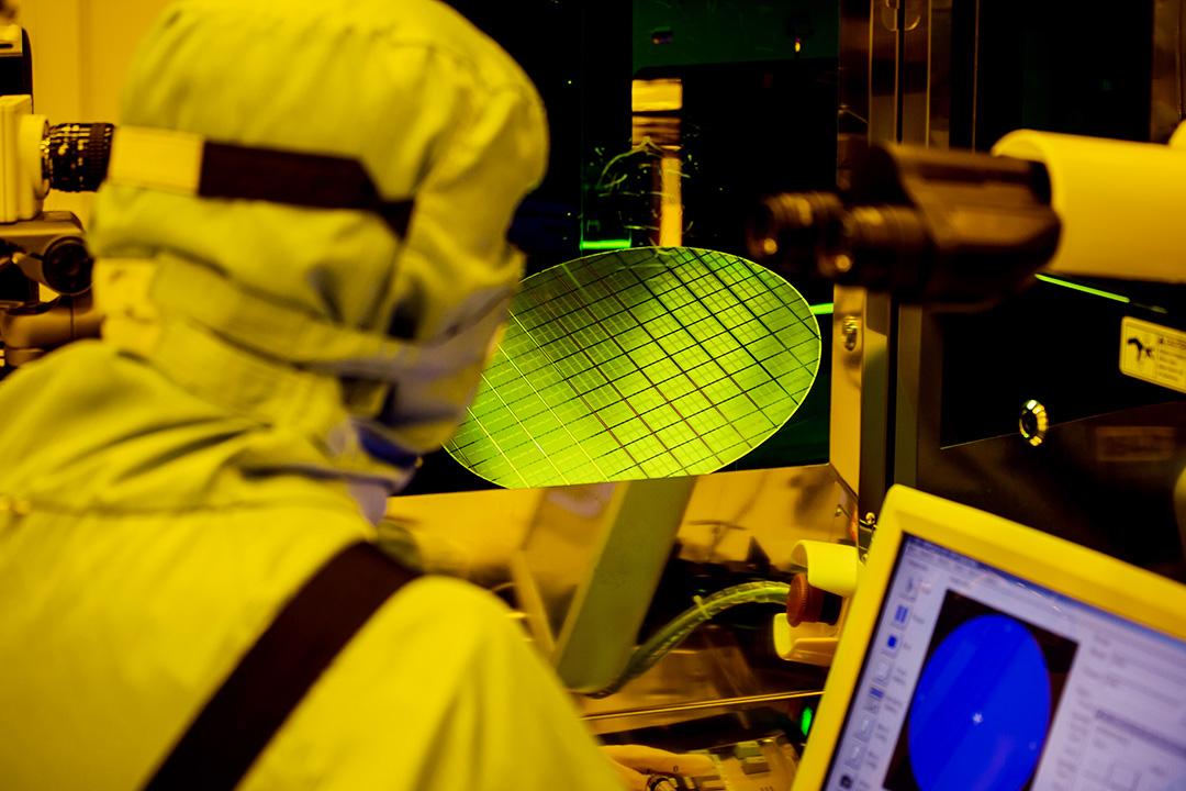 2016年4月26日台灣台中,矽品精密工業股份有限公司,一名員工於黃光照射的工作間以光學顯微鏡檢查晶圓。