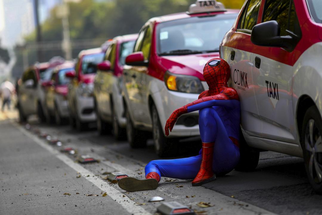 2020年10月12日,墨西哥墨西哥城有的士司機抗議Uber,一名打扮成蜘蛛俠的示威者坐在的士旁邊。