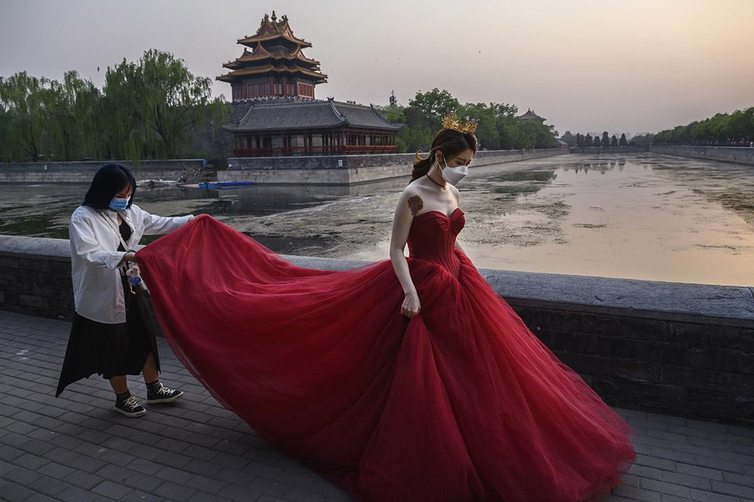 2020年4月30日北京,一名中國婦女戴著口罩在北京紫禁城外拍婚紗照。